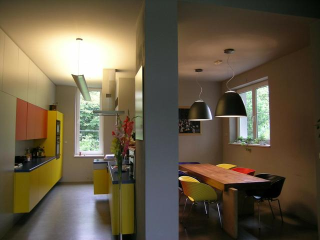 Contemporary-kitchen-with-wood-table-chairs-in-different-color-with-yellow-and-orange-cabinets-and-dark-floor